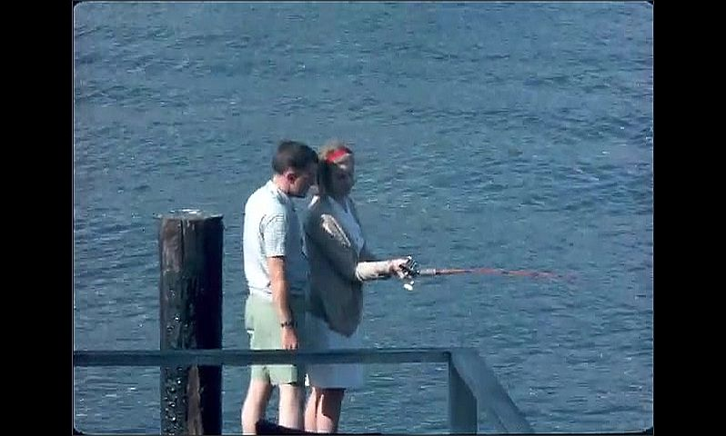 1950s: UNITED STATES: lady and man fishing from jetty. Lady with fishing rod casts off.