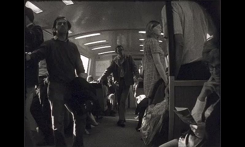1960s: UNITED STATES: passengers on train commute. View through window of train.