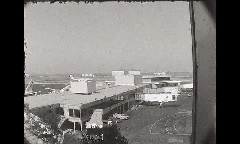 1960s: UNITED STATES: view of town from house. Planes at airport. View through lounge at airport. Plane on runway.