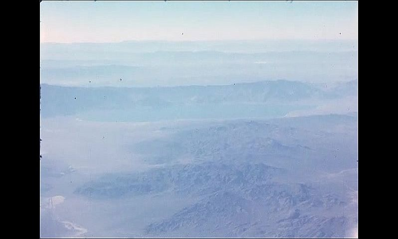 1960s: UNITED STATES: view of mountains and landscape from window of plane during flight. Lake view from plane window