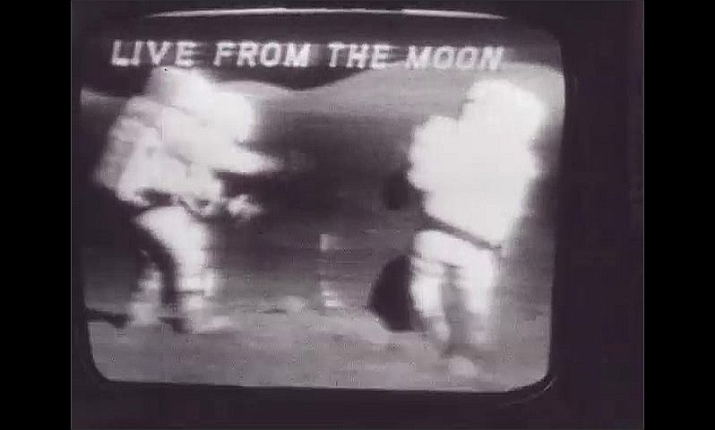 1960s: UNITED STATES: astronauts on moon live on television screen. Vintage television monitor of moon landing. Astronauts plant flag on moon.