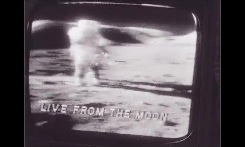 1960s: UNITED STATES: live from the moon footage on television screen in black and white. Astronaut on moon.