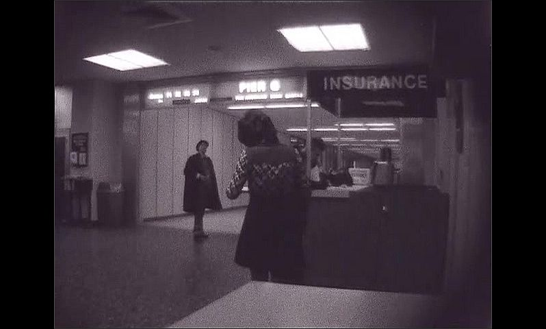 1960s: UNITED STATES: insurance counter. Man sets up camera. Pier 6 sign. Man points at sign.