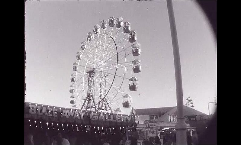 1960s: UNITED STATES: fairground rides at expo. People attend show. Cable car view of expo.
