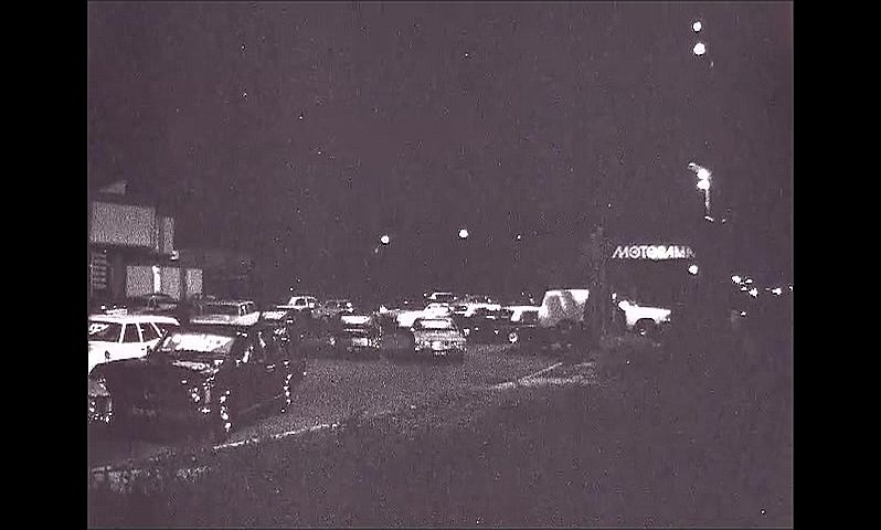 1960s: UNITED STATES: cars outside building at night. Parking lot at night. Worry Free Cars sign. Motorama sign.