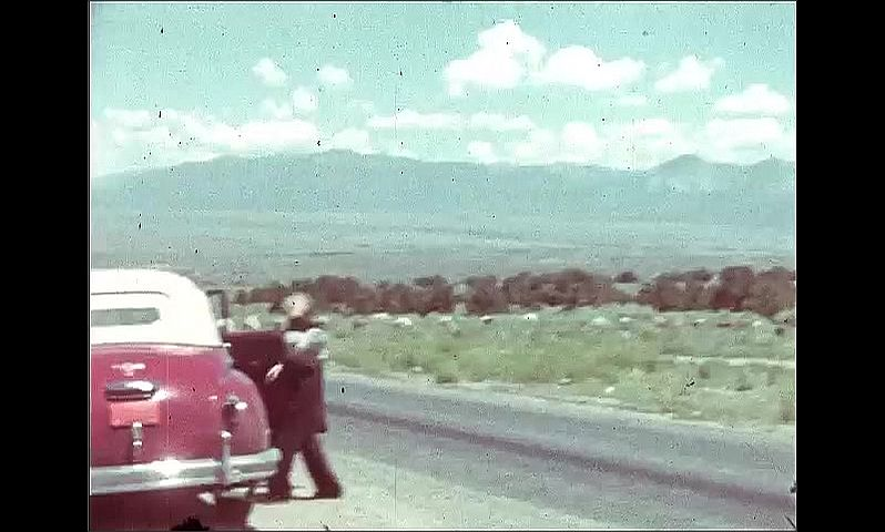 1940s: UNITED STATES: couple talk to local lady in street. Rio Grande Gorge sign. Lady prepares for hike by car. Buildings and horses in field.