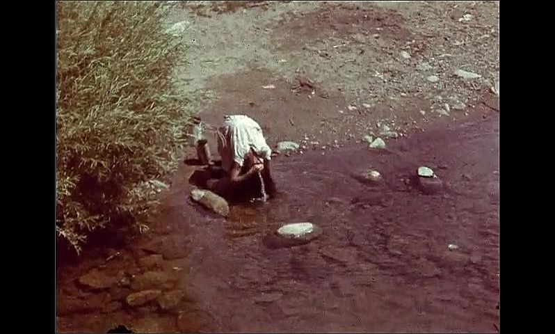 1940s: UNITED STATES: scaffold around building work. Girl washes hair in stream. Man with horse and cart on track.