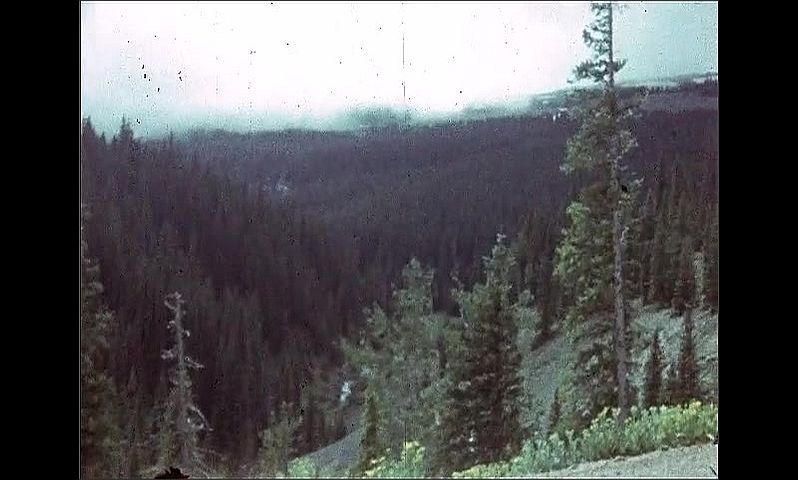 1940s: UNITED STATES: car drives along mountain track in Colorado. Clouds over forest. View of river in valley.