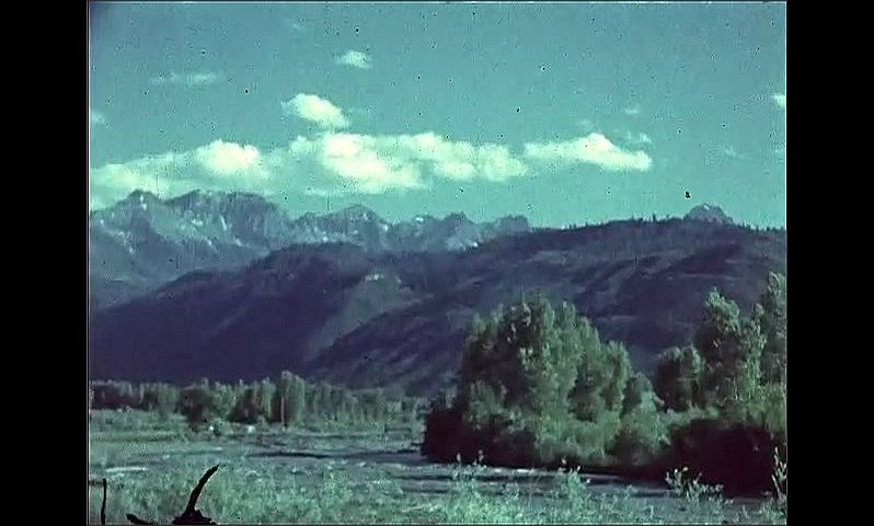 1940s: UNITED STATES: mountains and road through valley. Clouds over mountains. Black Canyon sign