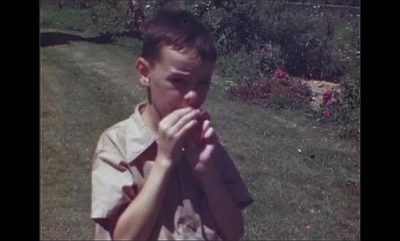 1940s: UNITED STATES: boy with remains of burst balloon. Boy blows up balloon. Girl with toy