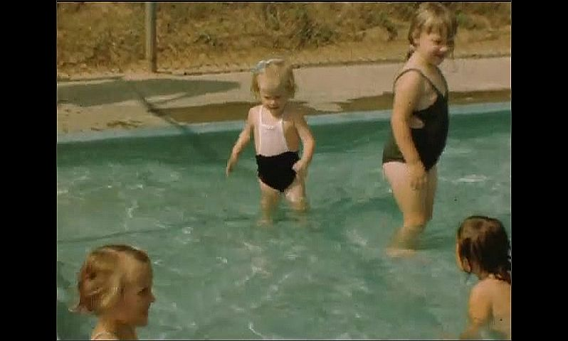 1940s: Little girl splashes in pool, climbs out of pool. Woman puts girl back into pool. Kids play in pool.