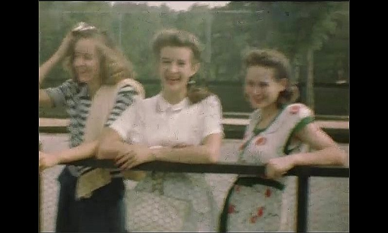 1940s: Women stand along fence, smile. Little girl sits on edge of pool. Kids play in pool.