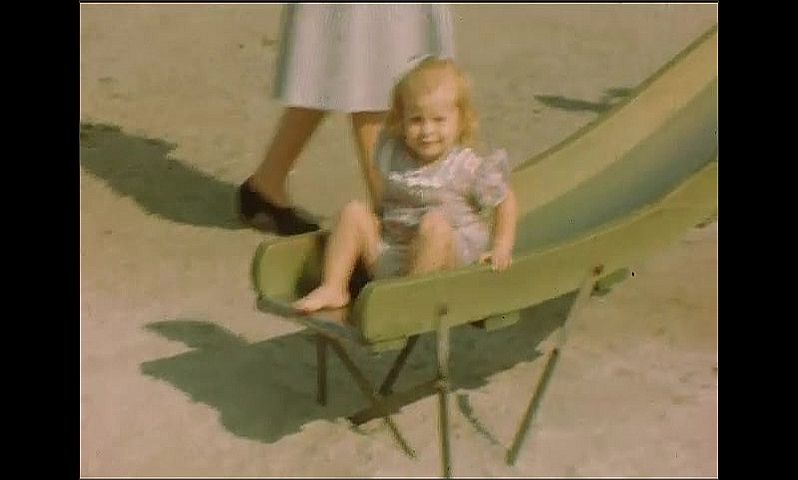 1940s: Young woman sits on edge of pool with little girl. Little girl slides down slide, walks across playground.