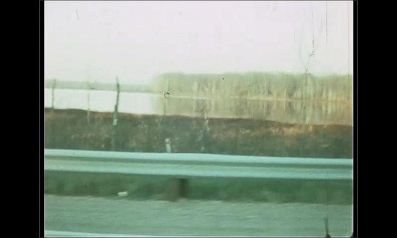 1960s: Car drives down two lane road. Lake.