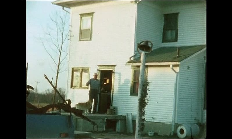 1960s: Man opens door of house, walks outside, waves. Dog greets man.