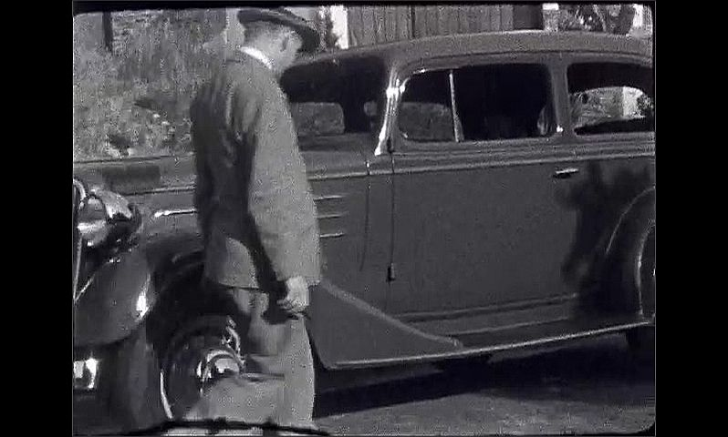 1940s: Two men kneel in front of car while working on it. Man stands looking at car then gets in driver's seat.