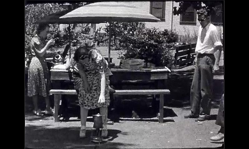 1940s: Looking at large body of water from dock. Men and women sit around picnic tables, talking.