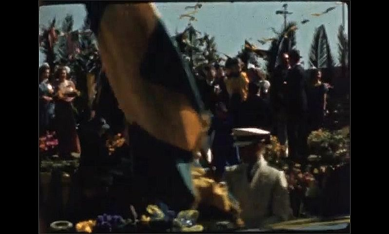 1940s: Band plays music for large audience. Woman in formal dress and tiara is assisted into convertible car.