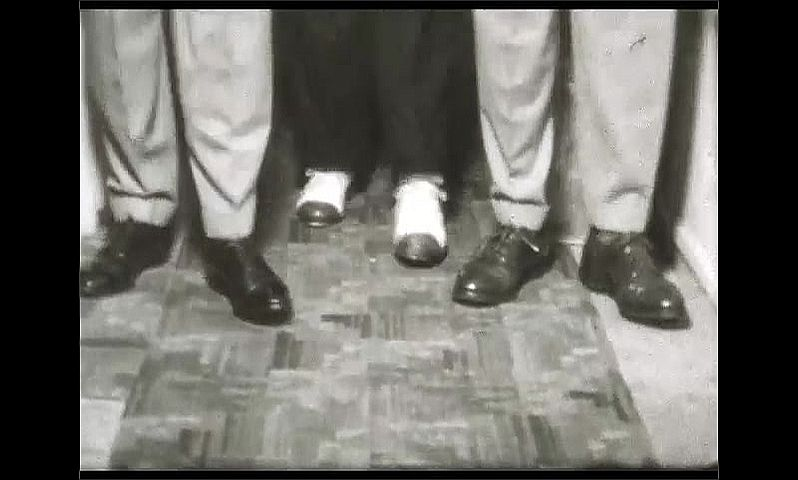 1940s: UNITED STATES: men get ready to go on stage. Men tap dance in corridor. Close up of feet dancing. Men in suits