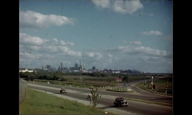 """1950s: Building.  Sign reads """"LOVE FIELD.""""  City.  Highway."""