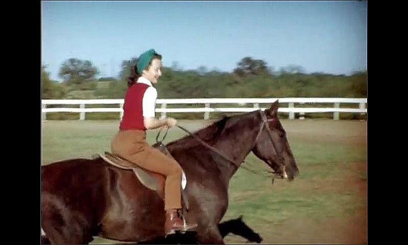 1950s: Women ride horses around track.