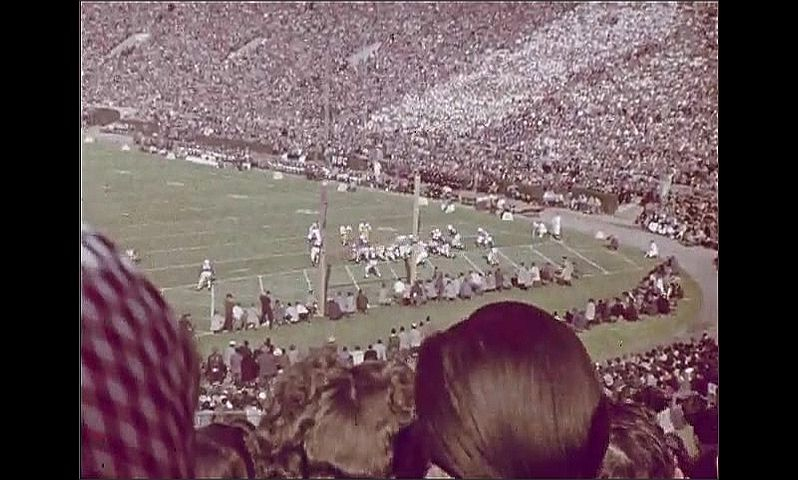 1950s: Stadium.  Football game.  Man jumps up and cheers.