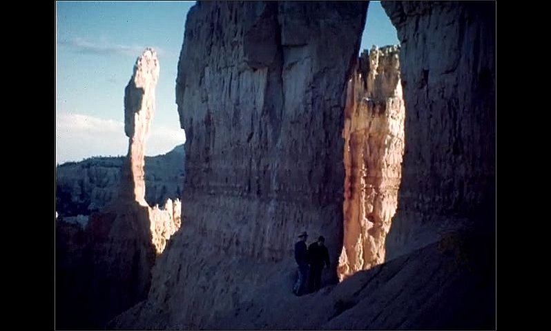 1940s: UNITED STATES: rock formations at Bryce Park and Peek-A-Boo Canyon. People walk over rocks in canyon. Arch through rocks