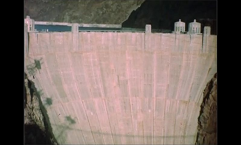 1940s: UNITED STATES: American flag flies against blue sky. View of Hoover Dam from above.