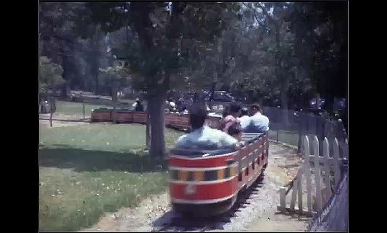 1940s: People ride miniature train around park. Passengers on train wave.