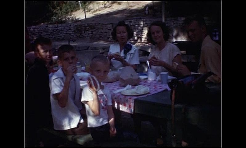 1940s: People sit at picnic table and eat.
