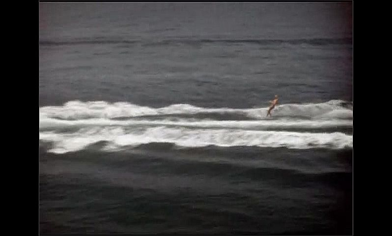 1940s: Boat speeds across water, man water skis behind boat.