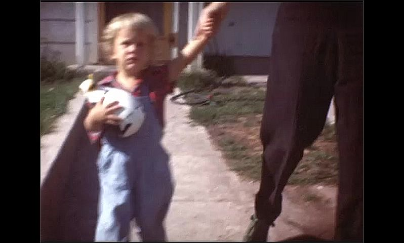 1940s: Woman walks out of house with toddler, holds child's hand. Child holds toy. Child plays with toy penguin on grass.