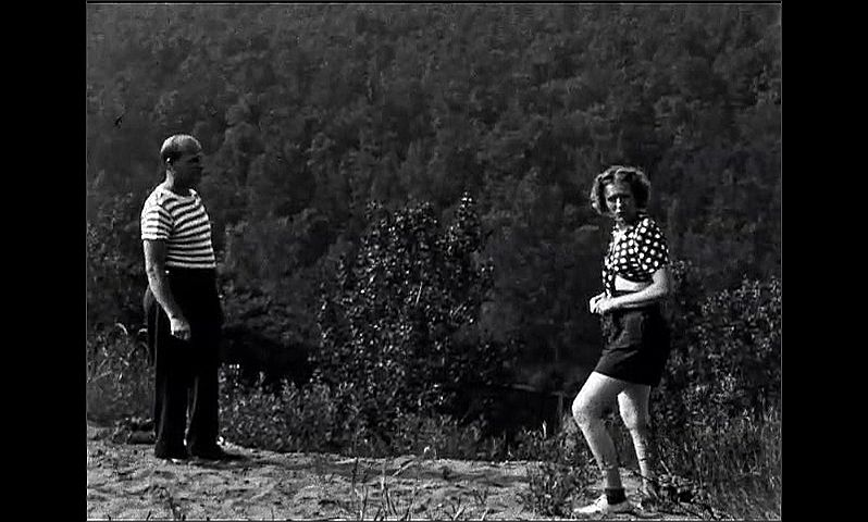 1940s: UNITED STATES: lady and man admire view. View across trees and forest from summit. View towards horizon across forest.