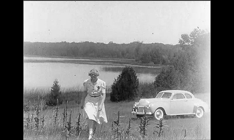 1940s: UNITED STATES: car parked in field by lake. Lady walks towards camera across grass. Man walks towards camera.