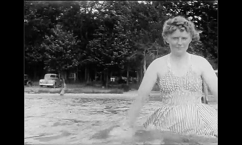 1940s: UNITED STATES: man swims in lake. Lady in dress in lake. View of road from car. Trees by road.