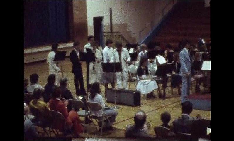 1970s: UNITED STATES: orchestra play in concert. People listen to music recital in hall.