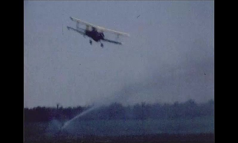 1970s: UNITED STATES: plane sprays crops from air.
