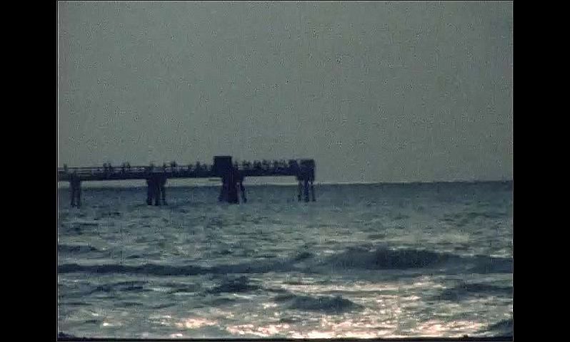 1970s: UNITED STATES: waves on beach at sunset. Pier by sea at sunset. Clouds over ocean at sunset. People on pier.