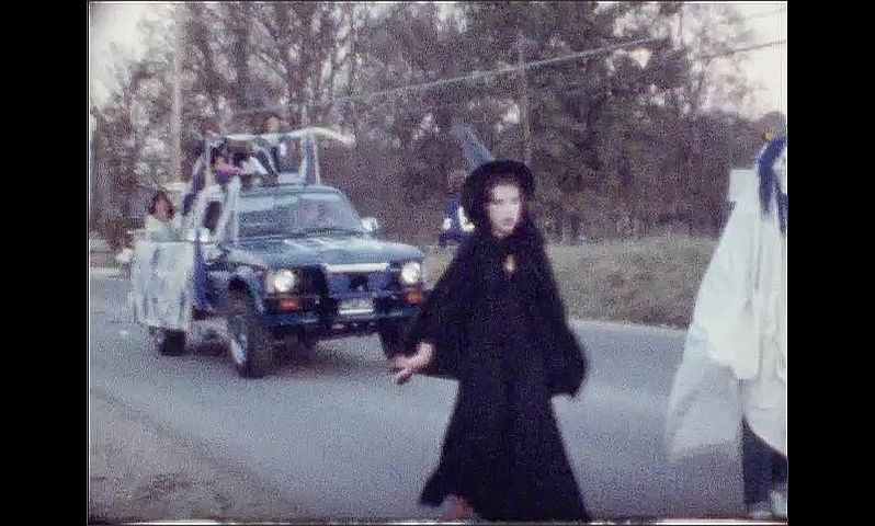 1970s: UNITED STATES: people in street parade. Person dressed as clown. Girl dressed as witch. Trucks in street parade.