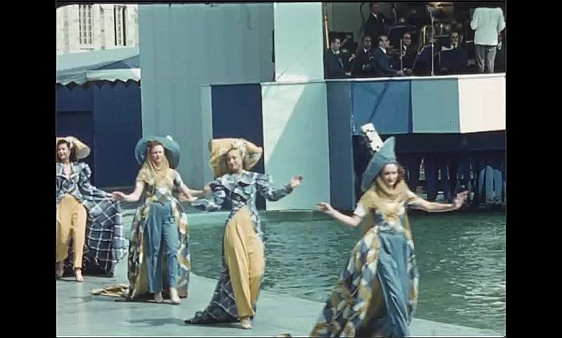 1930s: UNITED STATES: Aquacade dancers walk around pool. Ladies in costume and hats. Couple walk by water.