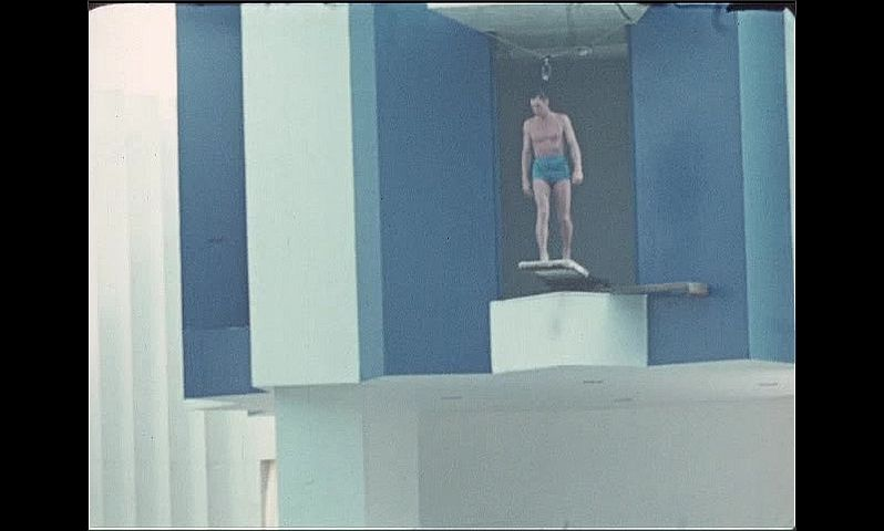 1930s: UNITED STATES: man on high dive board. Man performs show for crowd on high dive board. Man swims in water at Aquacade.