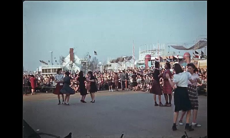 1930s: UNITED STATES: swing music and dancers. Ladies dance near band. Band play on stage. Man plays trombone. Brass instruments.