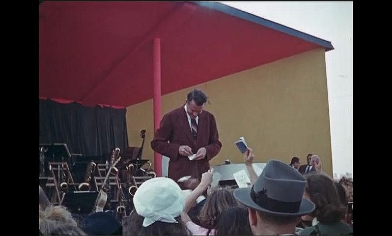 1930s: UNITED STATES: man on stage signs autographs for crowd. People wait for autographs.