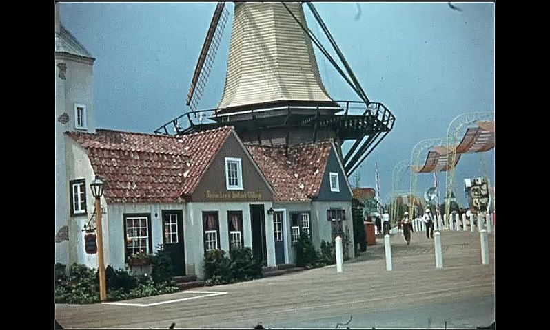 1930s: UNITED STATES: windmill with turning sails. American flag flies. Mill above building.