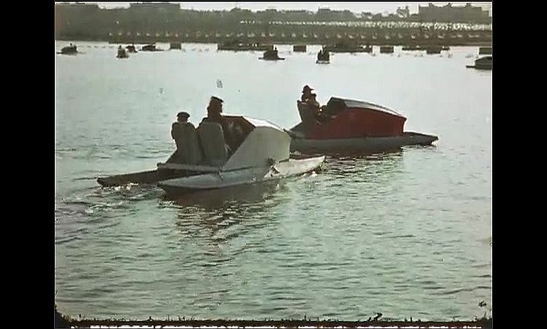 1930s: UNITED STATES: people on pedalo boats. Sunlight on water.