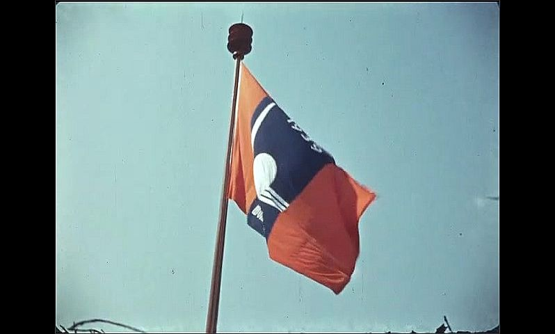 1930s: UNITED STATES: New York 1939 World Fair flag flies on pole. Blue sky. Red and blue flag on pole.