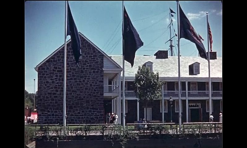 1930s: UNITED STATES: Replica of Trenton New Jersey Barracks. Sign outside barracks. Flags outside building.