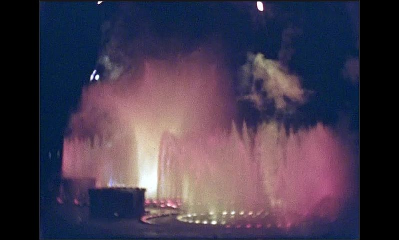 1930s: UNITED STATES: firework show around water fountain and lights.
