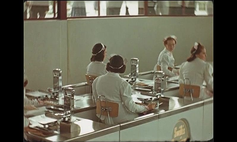 1930s: UNITED STATES: ladies work inside Swifts Premium Bacon factory room. People watch through glass.