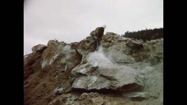 1960s: Man uses drill.  Bulldozer.  Mountain.